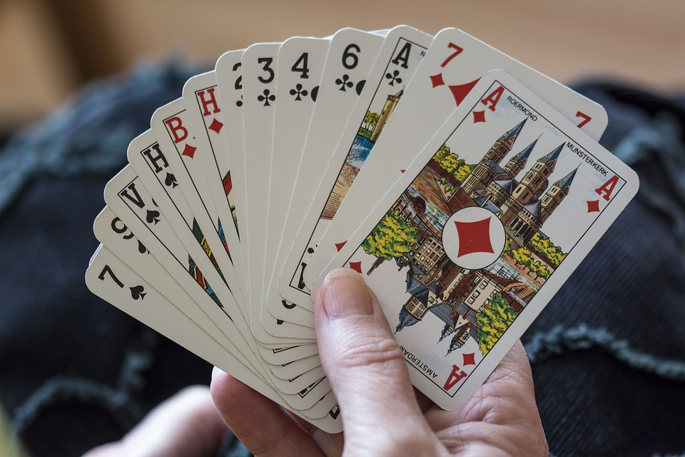 A right hand holding playing cards