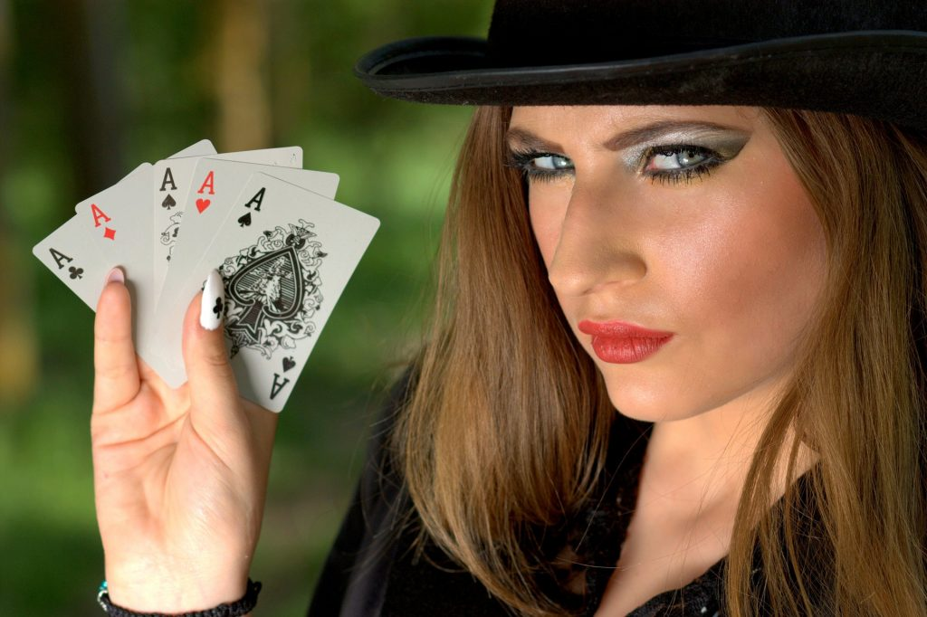 woman holding four aces