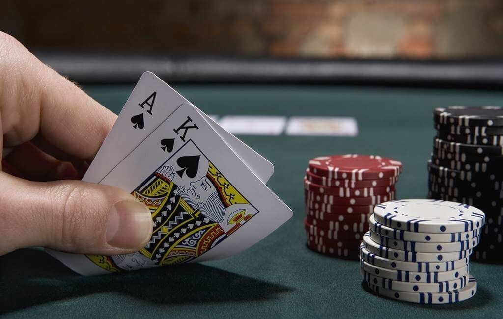 blackjack hand and poker chips