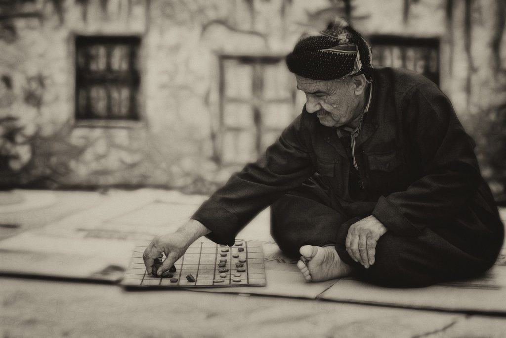 Old man playing checkers outdoors
