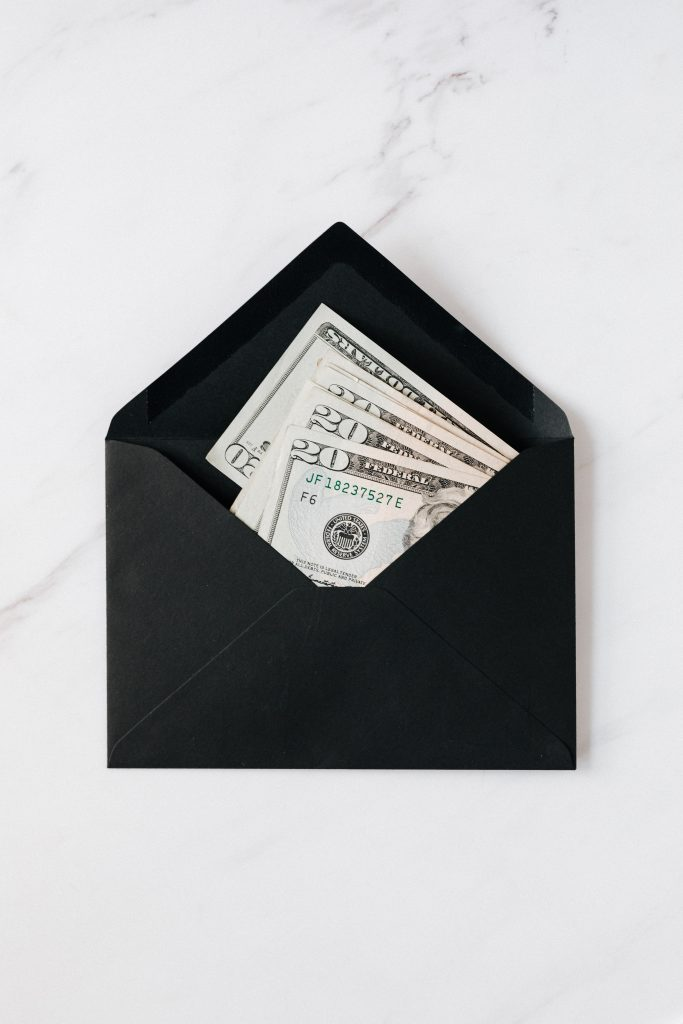 Black envelope with 20 dollar bills in it