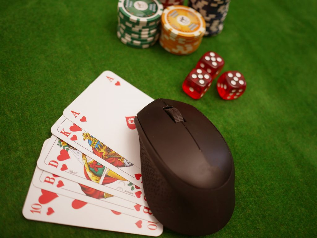 Mouse sitting on cards with dice and poker chips
