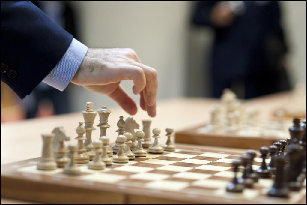 A man's hand picking up a chess piece