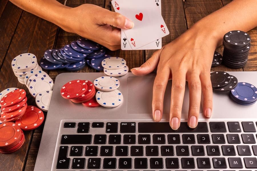 A hand holding aces with poker chips scattered all over a laptop