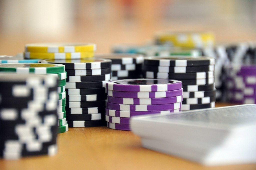 Poker chips in focus with blurred playing cards